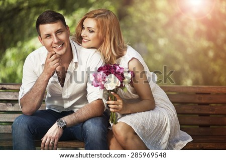 Young romantic couple sitting on bench in the park and  smiling. Love concept. - stock photo