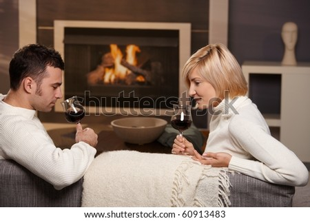 Young romantic couple sitting on sofa in front of fireplace at home, drinking red wine.