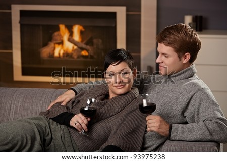Young romantic couple sitting on sofa in front of fireplace at home, drinking red wine.?