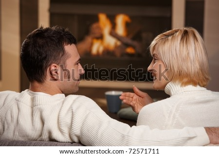 Young romantic couple sitting on sofa in front of fireplace at home, looking at each other, talking, rear view.? - stock photo