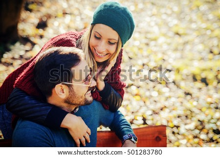 Young romantic couple sitting on the bench in autumnal park on sunny day. Concept of relationship and love
