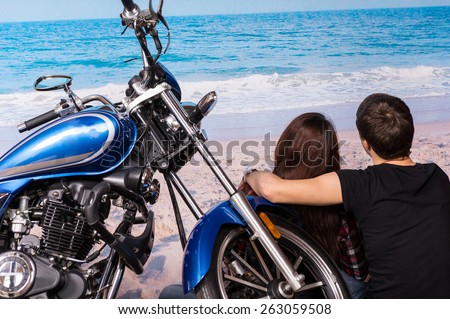 Young Romantic Couple Sitting with Arms Around Each Other on Sandy Beach with Motorcycle - stock photo