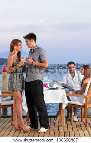 Young romantic couple standing close together on a wooden deck overlooking the sea drinking white wine