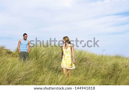Young romantic couple walking in tall grass at beach - stock photo