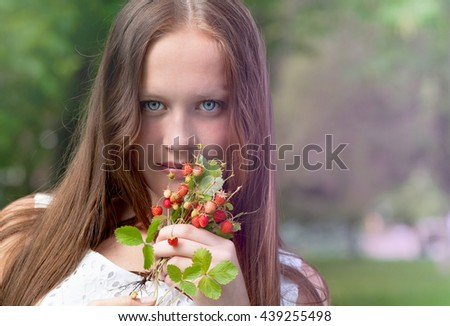 Young, romantic girl with strawberry field. - stock photo