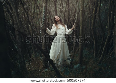 Young romantic woman in desolate autumn forest . Innocence and loneliness