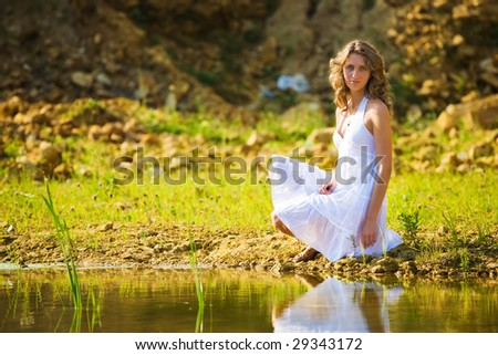 Young romantic woman on a river bank.