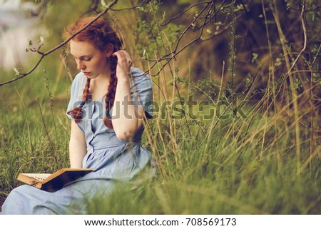 Young romantic woman reading a book sitting on the grass