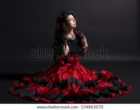 Young romany woman sit in spanish traditional clothes