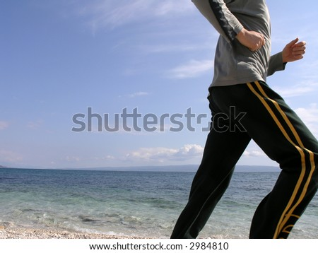 Young runner in motion at the beach - stock photo