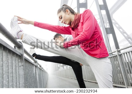 young runner stretch muscles before the race - stock photo