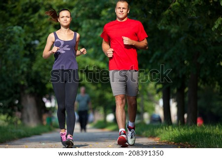 Young running couple jogging in nature - stock photo