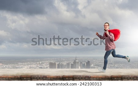 Young running girl with red santa bag in hands