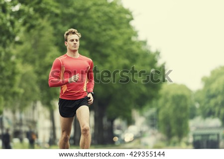 Young running man in the city. Caucasian Cheerful jogger male in his 20s - stock photo