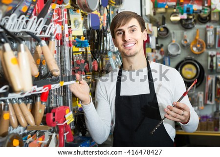 Young russian male seller posing at tooling section of household store