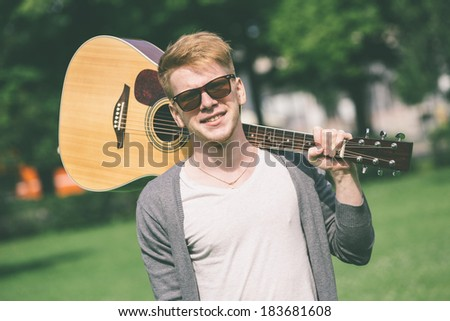 Young Russian Man Holding Guitar - stock photo