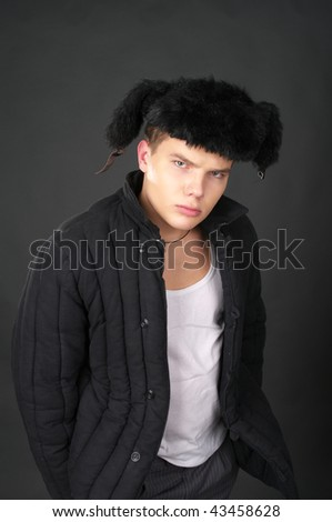 Young russian man in the fur cap with ear-flaps