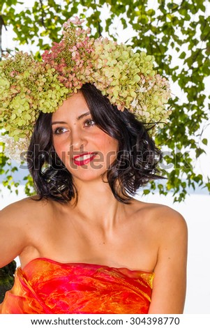 young Russian woman on her head a wreath of flowers hydrangeas, a woman relaxed, reclining on a tree trunk, happy, Russian traditions and folk life, lifestyle and clothing, intimate nature,