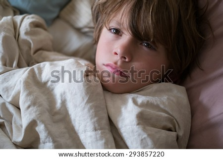 young sad ( boy) child laying in bed - stock photo