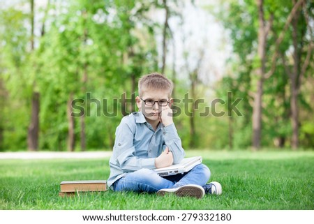 young sad boy with a books and laptop computer on green grass in the park - stock photo