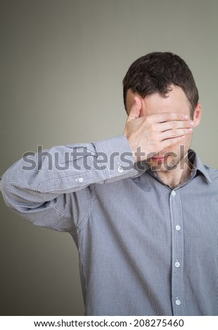Young sad Caucasian man hiding his face with hand - stock photo