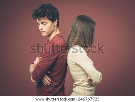 Young sad couple arguing and standing back to back