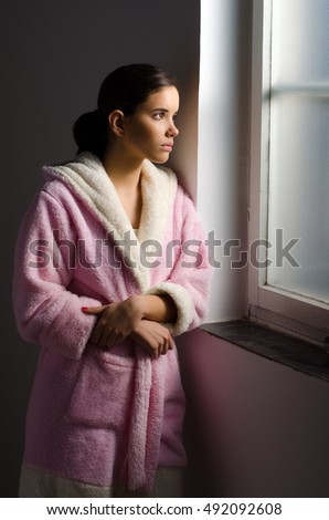 Young sad girl, cancer patient looking through hospital window.