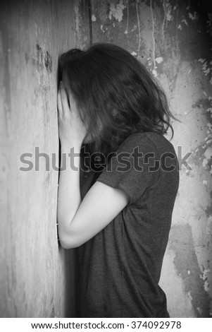 Young sad girl in the corner of  room - stock photo