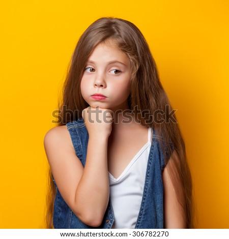 Young sad girl on yellow background. - stock photo