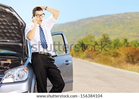 Young sad male on a broken car talking on a cell phone
