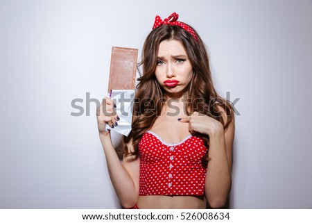 Young sad model in underwear with chocolate. isolated gray background
