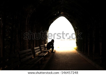 young sad sitting in the dark tunnel - stock photo
