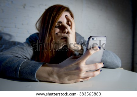 young sad vulnerable girl using mobile phone scared and desperate suffering online abuse cyberbullying being stalked and harassed in teenager cyber bullying concept - stock photo