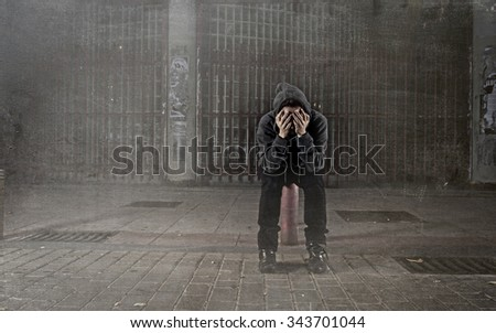 young sad woman alone wearing hoodie on street suffering depression looking  desperate and helpless sitting lonely in urban night background in female victim of abuse concept grunge dirty edit - stock photo