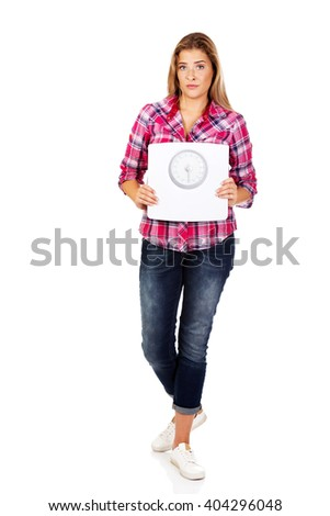 Young sad woman holding weight scale - stock photo