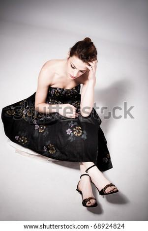 young sad woman in elegant dress sit on floor, studio shot - stock photo