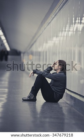 young sad woman in pain sitting alone and depressed at urban subway tunnel ground looking worried and frustrated covering her face suffering depression in female loneliness concept  - stock photo