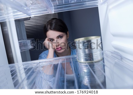 Young sad woman looking at one tin in her empty fridge. - stock photo
