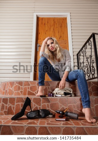 Young sad woman lost her house keys. Girl sits in front of the door - stock photo