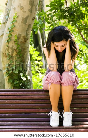 Young sad woman sitting on a park bench. - stock photo