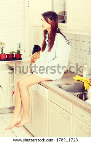 Young sad woman sitting on kitchen counter wearing men's shirt
