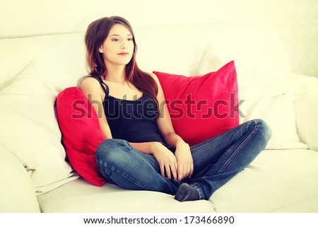 Young sad woman sitting on sofa at home