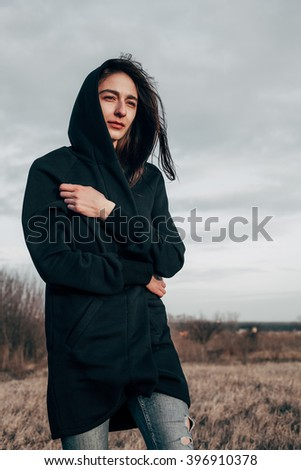 Young sad woman walking on the field in windy weather