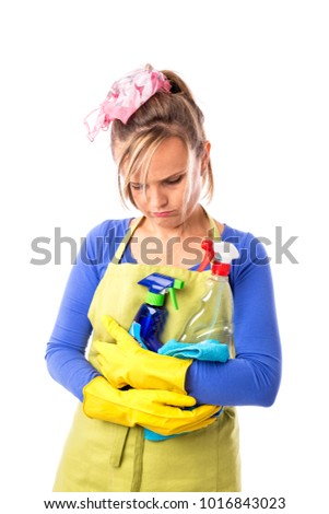 Young sad woman with apron and yellow gloves holding cleaning products isolated on white background.