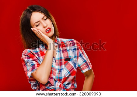 Young sad woman, with short dark hair, wearing in checkered shirt, posing on red background, in studio, waist up - stock photo
