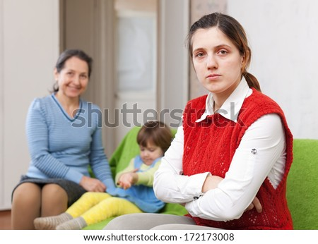 young sadness mother and grandmother with baby after quarrel at home - stock photo