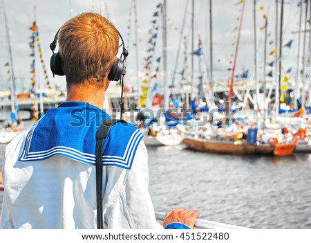 Young Sailor in headphones on the Shore Looking at the Boats