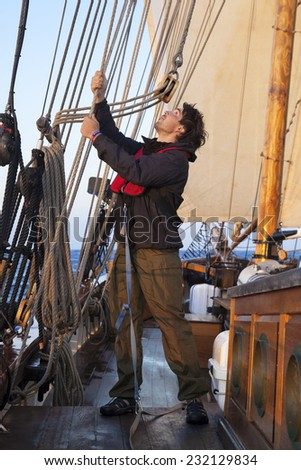 Young sailor on a ship's deck hoisting a sail - stock photo