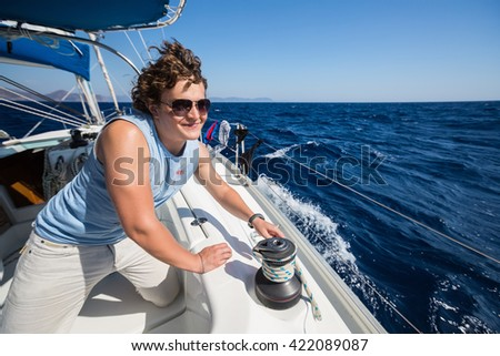 Young sailor on the yacht working with rope on the winch