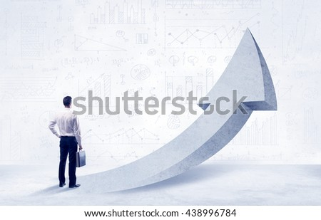 Young sales business person in elegant suit standing with his back in front of a big arrow pointing up and a clear background full of pie charts, numbers - stock photo
